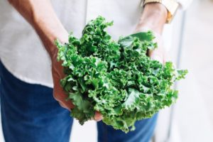 A man holding kale