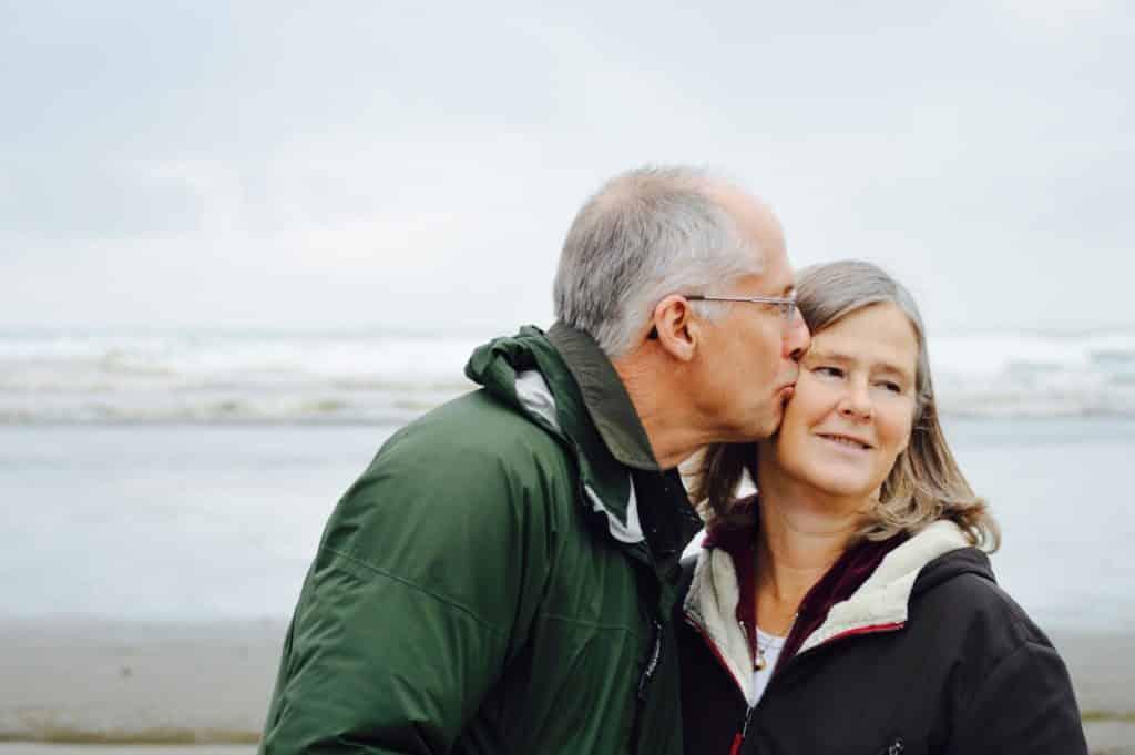 An elderly couple kisses on the beach
