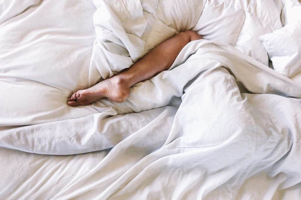An anonymous leg peaks out from underneath white sheets