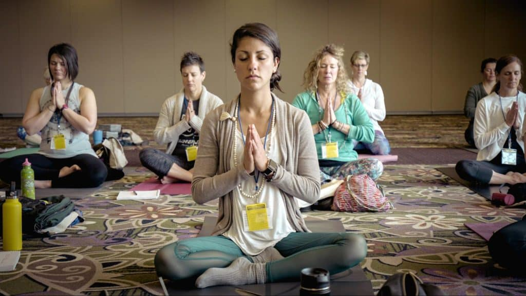 A group of women at a conference meditate together