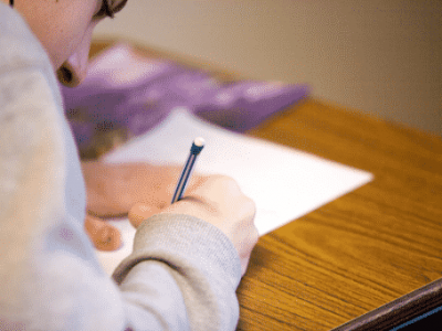 A person writing on paper with a pencil